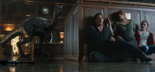 Jurassic World: Das gefallene Königreich mit Chris Pratt und Bryce Dallas Howard, die sich vor einem Dinosaurier verstecken